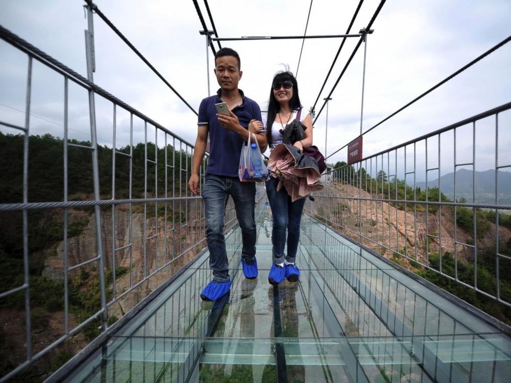 туристы на мосту из стекла